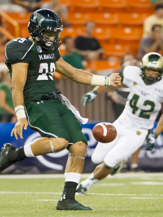 FILE - In this Oct. 26, 2013, file photo, Hawaii wide receiver Scott Harding (29) punts the football as Colorado State linebacker Ken Hulbert (42) looks on in the third quarter of an NCAA college football game in Honolulu. Harding can kick running in both directions, with either foot. Occasionally, he'll try to hit the defensive players in the back to create a turnover. The rugby style of punting he uses, that's spreading across college football. (AP Photo/Eugene Tanner, File)