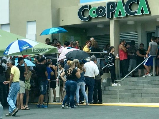 Customers in Puerto Rico wait in a long line to withdraw