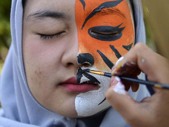 A student gets her face painted during an Earth Day