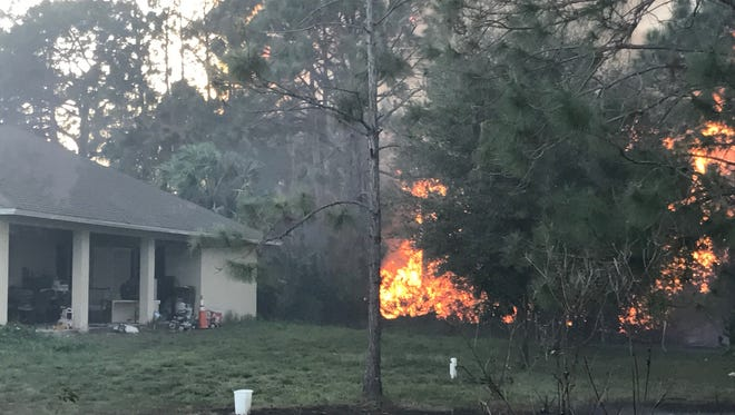 A brush fire rages very close to a home in Lehigh Acres on Sunday. Many homes were threatened and roads had to be closed in the region.