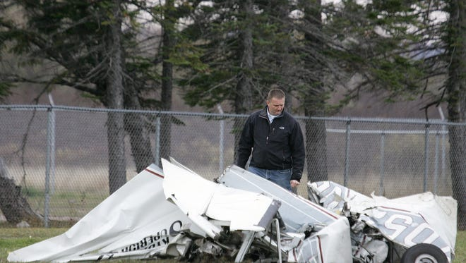 An FAA investigator examines the wreckage of a plane that crashed in Superior, Wis., Saturday after a midair collision with another plane.