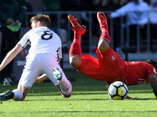 New Zealand's Michael McGlinchey, left, tackles Peru's Yoshimar Yotun during their Soccer World Cup qualifying match in Wellington, New Zealand, Saturday, Nov. 11, 2017. ( (Ross Setford/SNPA via AP)