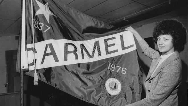 Peggy Lou Smith displays the newly adopted Carmel city flag, which she designed in 1976.