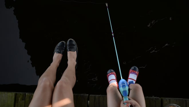 """Lansing resident Carly Cosper and her daughter Rosie, 5, fish at Adado Riverfront Park on Saturday, June 11, 2016 during the Grand American Fish Rodeo Festival. June 11 and 12 is Michigan's Free Fishing Weekend. """"We like to get out on the weekends,"""" Carly said. """"(My daughters) are interested in the outdoors. When it's other people teaching the kids it's a different way to teach them things. They're more apt to listen to other people sometimes."""" The U.S. Fish and Wildlife Service was there teaching children about different aquatic wildlife and how to fish."""