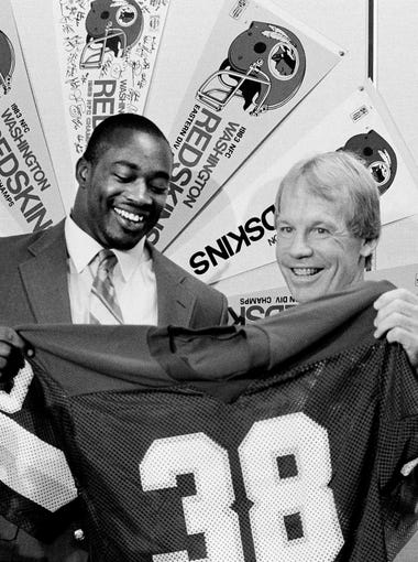 Bobby Beathard, right, general manager of the Washington Redskins, and the team's latest acquisition, running back George Rogers, unveil his new jersey during a press conference at Redskins Park in Chantilly, Va. April 26, 1985. Rogers was traded by the New Orleans Saints.