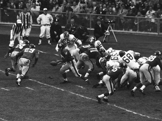 New York Giants quarterback Y.A. Tittle (14) hands football off to fullback Alex Webster (29) who goes for touchdown. Action took place in second quarter of game against the Philadelphia Eagles at New York?s Yankee Stadium on Nov. 10, 1963. (AP Photo)