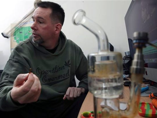 In this Feb. 26, 2016 photograph, a marijuana pipe is nearby, as former U.S. Marine, Mike Whiter answers a question about his marijuana use to treat post-traumatic stress disorder, at his home in Philadelphia. A growing number of states are weighing whether to legalize marijuana to treat PTSD. While the research has been contradictory and limited, some former members of the military say marijuana helps them manage their anxiety, insomnia and nightmares. (AP Photo/Mel Evans)