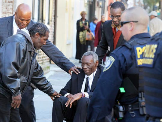 John Pinckney, father of shooting victim Rev. Clementa Pinckney, is greeted after leaving J. Waites Waring Federal Courthouse in Charleston, S.C., Thursday, Dec. 15, 2016, where Dylann Roof was found guilty of all 33 federal charges in the Emanuel AME Church shootings.