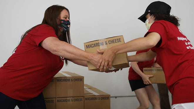 Barbara Sargent of Weymouth hands a box of macaroni and cheese to Samantha Coyle of Weymouth while helping break down a pallet at the warehouse for the Weymouth Food Bank on Thursday, June 4, 2020.