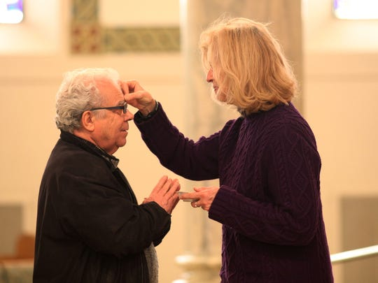 Joaquim Flores receives ashes from Marilyn Catherine