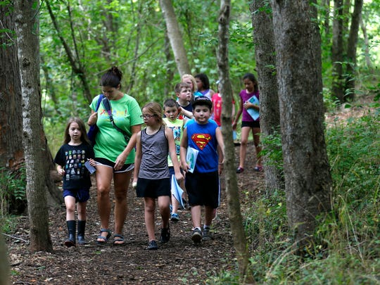 Sarah Call, a site teacher with Springfield Public Schools, leads a class from Cowden Elementary on a trail at the Watershed Center at Valley Water Mill Park during summer school on Wednesday, July 13, 2016.