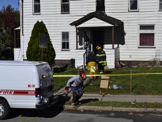 Firefighters and other officials investigate the fire
