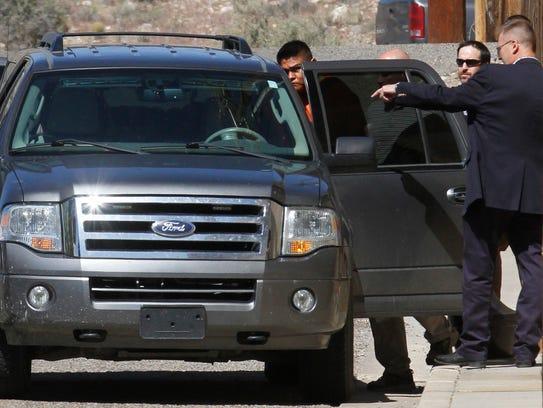 Law enforcement officials escort Tom Begaye after he