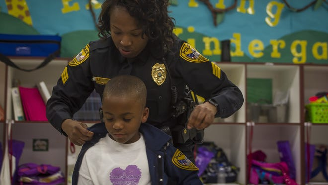 Sgt. Anitra Highland helps  Bryce Eric Owens put on his new Junior officer uniform. The 5- year old kindergarten student has been selected by March of Dimes to be a local ambassador for Tallahassee.