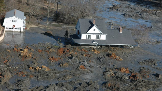 "In a Dec. 22, 2008, photograph, a home is engulfed near TVA's Kingston Fossil Plant in Roane County  after the failure of a storage cell unleashed 5.4 million cubic yards of ash sludge. U.S. District Judge Thomas Varlan ruled that ""TVA is liable for the ultimate failure of North Dike which flowed, in part, from TVA's negligent nondiscretionary conduct."" (J. Miles Cary/News Sentinel)"