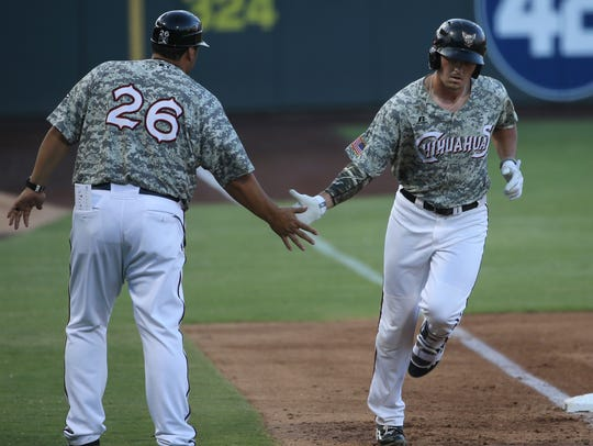 El Paso's Hunter Renfroe is congratulated by manager