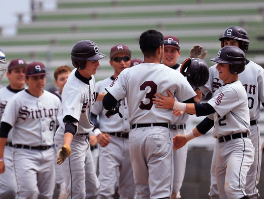 Sinton players congratulate Jordan Martinez (3) after