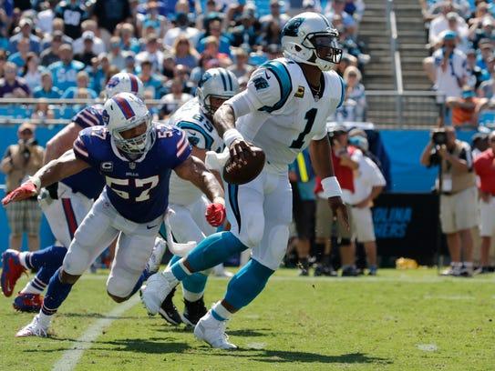 Carolina quarterback Cam Newton scrambles past Bills