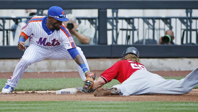 Washington Nationals Jayson Werth safely steals third base as Mets third baseman Jose Reyes applies a late tag during the third inning of Sunday's game.