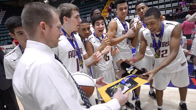 Aquinas head coach Michael Grosodonia, left, hands the championship plaque to Jalen Pickett following the Class AA final of the 2016 NYSPHSAA Boys Basketball Championships held at the Glens Falls Civic Center in Glens Falls on March 13, 2016.