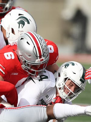 Michigan State's Brian Lewerke is tackled by Ohio State's Sam Hubbard in the second quarter Saturday.