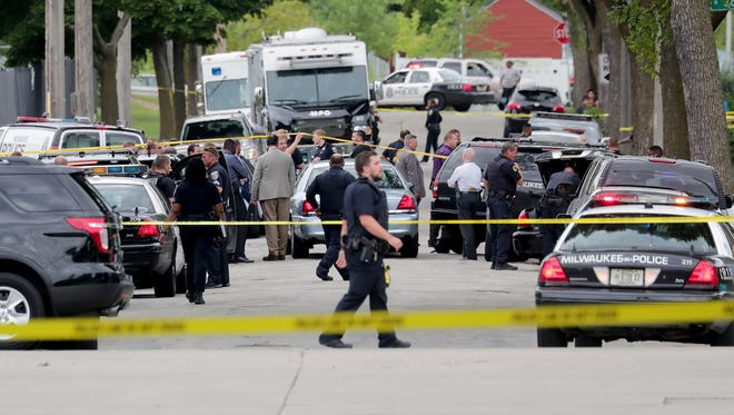 Law enforcement officers investigate the scene where a Milwaukee police officer was fatally shot Wednesday evening.