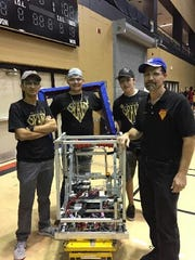 From left, Martin County S.P.A.M. students Shantanu Jakhete, Dawson Sturgill, Michael Sansevere and Mentor James Jones. On the first day of competition, after the robot has been unbagged officially, the Pit Crew stands in line for Robot Inspection where the bots are weighed, measured and reviewed to be in compliance with building and safety rules. Teams are not allowed on the competition field until their robots pass inspection.
