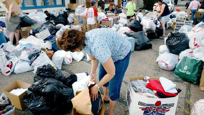 Volunteers begin carrying items to a waiting semitrailer after collection of clothing and other items began at the St. Cloud Housing Coalition offices for victims of Hurricane Katrina on Labor Day in 2005.