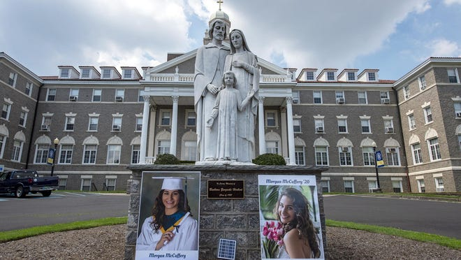 Photos of dating violence victim Morgan McCaffrey, a 2020 graduate of Nazareth Academy in Philadelphia, rest next to the Holy Family statue in front of the high school.