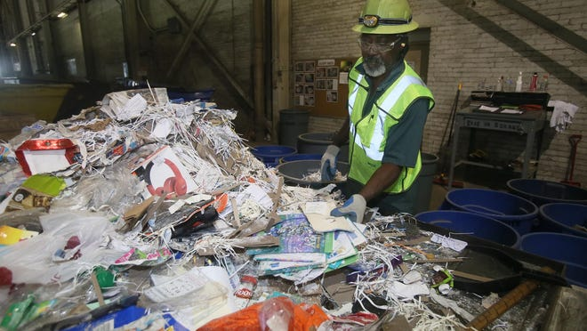 In this 2018 Beacon Journal file photo, Jeff Rodgers, a recycle auditor at Waste Management's Materials Recovery Facility in Akron, sorts through a selection of recyclable material to assess how much has been properly sent for recycling.