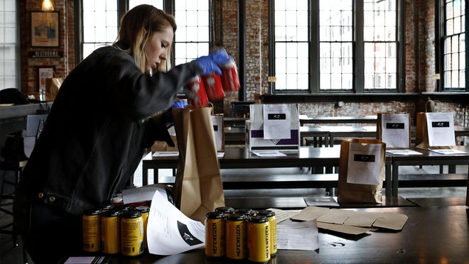 Wolf's Ridge Brewing employee Lila Moore packs carryout orders of beer. The brewry and restaurant reopened its dining area after Gov. Mike DeWine permitted it, but closed it again to ensure the safety of customers and employees.