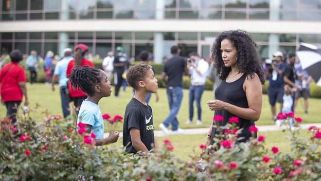 Jenny Moman talks with her daughter, Olivia Booker, 9, and her nephew, Jace Brown, 8, outside Fountain of Praise church in Houston, site of George Floyd's public memorial service Monday.