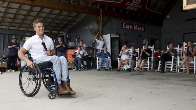 Supporters cheer during an Independence Day speech by N.C. Congressional District 11 Republican nominee Madison Cawthorn, left, at Grandad's Apples N' Such this summer.