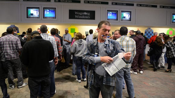 Rob Gwinn of Louisville checks his tickets by the betting window during the opening night of Churchill Downs' 2013 Spring Meet.