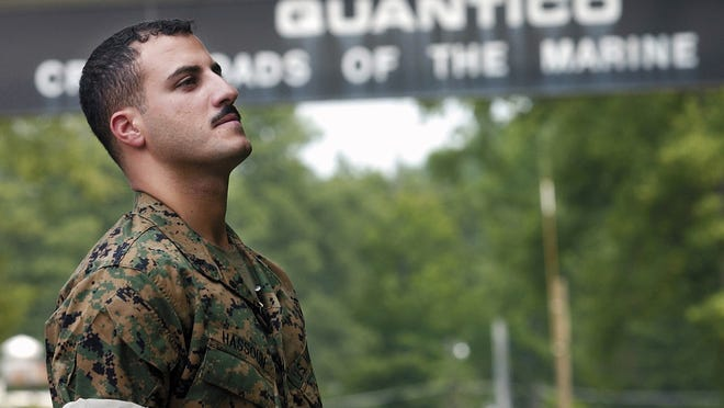 In this July 19, 2004, file photo U.S. Marines Cpl. Wassef Ali Hassoun prepares himself as he waits to make a statement to a large crowd of media outside the gates to the USMC base in Quantico, Virginia. Nearly 10 years ago Hassoun was declared a deserter after allegedly faking his own kidnapping in Iraq, then reappeared and was to face charges. But he disappeared again in 2005, has now turned himself in to U.S. authorities.