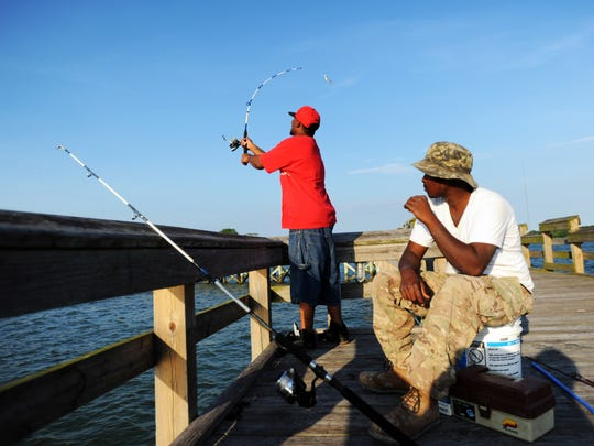 Wayne Robinson watches Shawn Smith cast his line in the water as he takes a break to catch a quick bite while fishing at the Cape Charles pier on Tuesday, July 1, 2014.