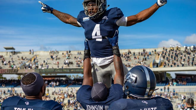 Redshirt freshman running back Gerald Green is lifted up by senior defensive end Raymond Johnson III after Green' 69-yard touchdown run -- the first of his career -- against Troy on Nov. 7 at Paulson Stadium in Statesboro.