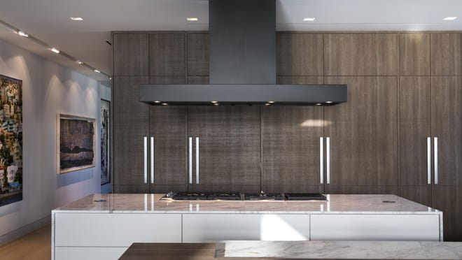 The custom cladding appliance fronts and cabinetry create an integrated, serene sight line throughout an open plan kitchen and living space in this Miami Beach penthouse project designed by the Coral Gables, Fla.-based design firm Dunagan Diverio.