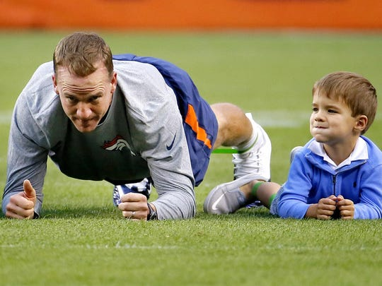 Peyton Manning warms up with his son, Marshall, 4, prior to an exhibition game.