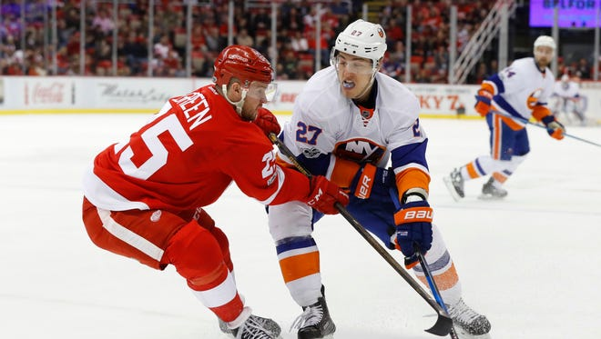 Red Wings defenseman Mike Green defends Islanders left wing Anders Lee in the first period Tuesday, Feb. 21, 2017 in Detroit.