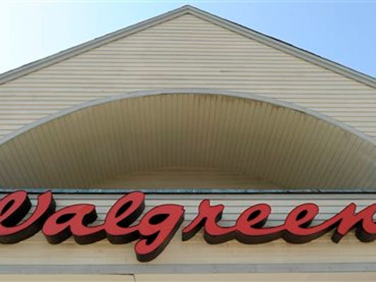 FILE - The sign above a Walgreens entrance, is seen in this Sept. 28, 2009 file photo taken in Gloucester, Mass. Walgreens plans to close about 200 U.S. stores as the nation's largest drugstore chain expands on a $1 billion cost-reduction plan it announced last August.