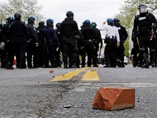 A brick sits on a street as police standby, Monday, April 27, 2015, during a skirmish with demonstrators after the funeral of Freddie Gray in Baltimore. Gray died from spinal injuries about a week after he was arrested and transported in a Baltimore Police Department van.