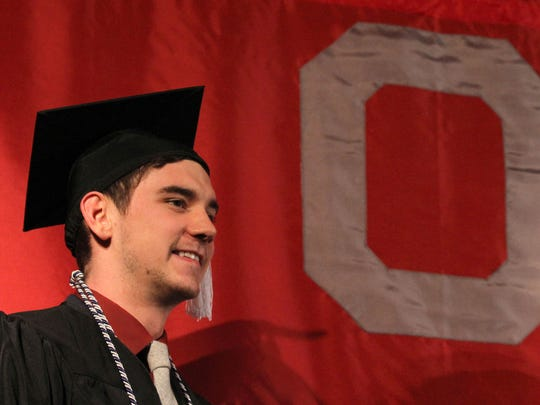 Joseph Burley stands next to a banner during The Ohio State University at Mansfield campus graduation ceremony at Founder Auditorium on Thursday evening.