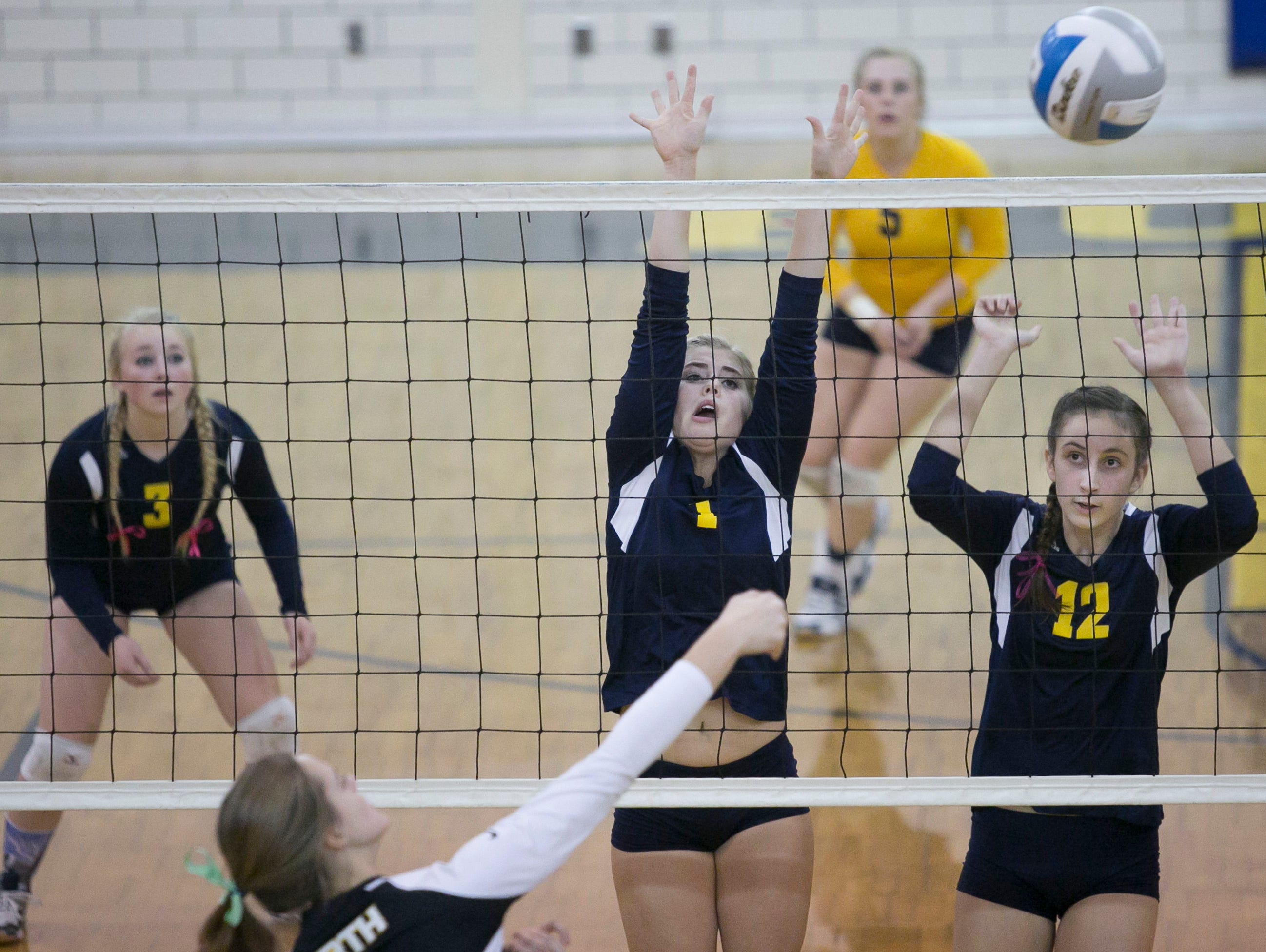 Port Huron Northern junior Brooke Bowerman and sophomore Halle Shell jump to block a spike during a volleyball game Tuesday, October 27, 2015 at Port Huron Northern High School.