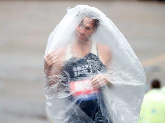 Runner Kyle Rodemacher struggles with his poncho prior to the 2019 Boston Marathon.