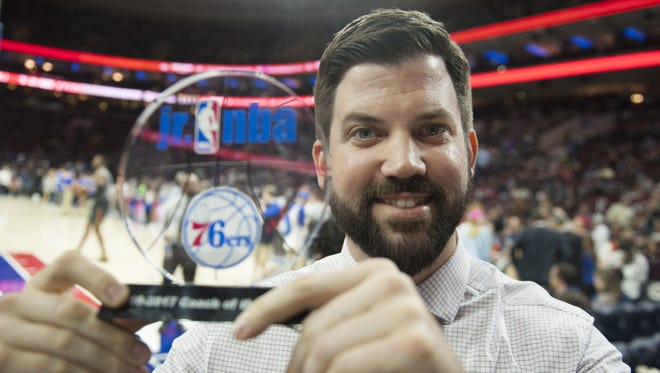 Matt George, basketball coach at KIPP Lanning Square Middle School in Camdne, displays the Jr. NBA Coach of the Year award that he received at halftime of the Sixers/Hawks game in Philadelphia on Wednesday.