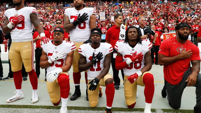 Members of the San Francisco 49ers kneel and stand during the playing of the National Anthem before an NFL football game against the Washington Redskins in Landover, Md., Sunday, Oct. 15, 2017. Kneeling are (L-R) strong safety Eric Reid (35), wide receiver Marquise Goodwin (11) and defensive back Adrian Colbert (38).