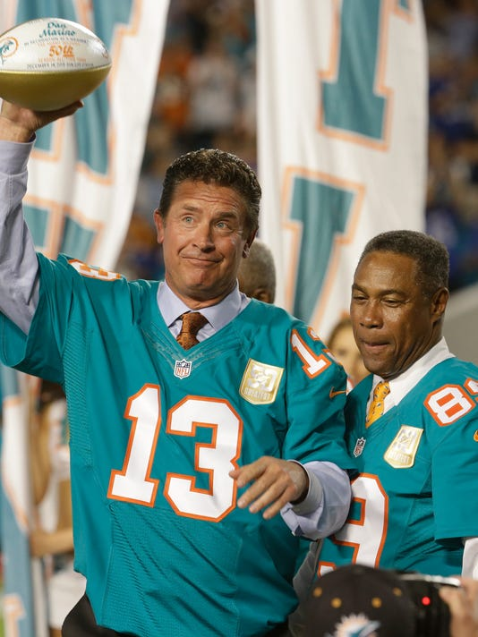 Former Miami Dolphins quarterback raises a commemorative football during a half time ceremony celebrating the Dolphins All -Time 50th Anniversary Team during a half time ceremony at an NFL football game against the New York Giants,  Monday, Dec. 14, 2015, in Miami Gardens, Fla.  (AP Photo/Lynne Sladky)