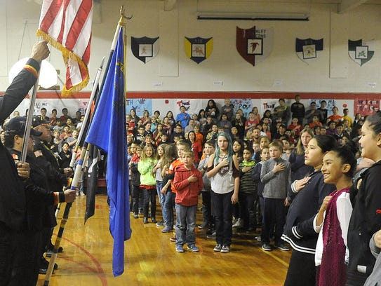 Students pledge allegiance to the flag during the assembly.