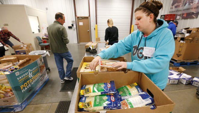 Volunteer Cienna Bridges repackages lunch meat on Tuesday, Jan. 12, 2016 at the Ozarks Food Harvest. Ozarks Food Harvest was notified this month of its four star rating from Charity Navigator.